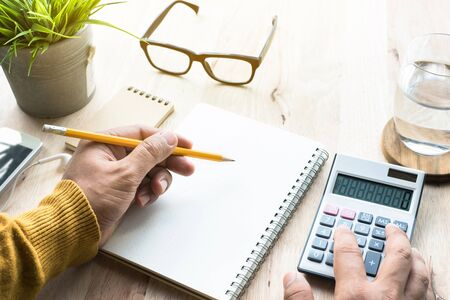 Male working with calculator and notepad on worktable.business plan,financial,lifestyle concepts