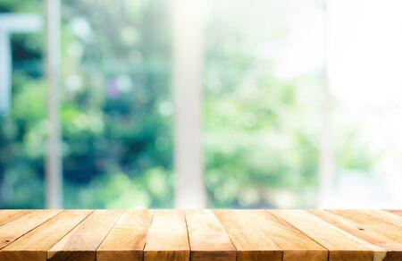 Mesa de madera en el desenfoque de la ventana con fondo de flores de jardín en la mañana. Para la exhibición del producto de montaje o el diseño visual clave