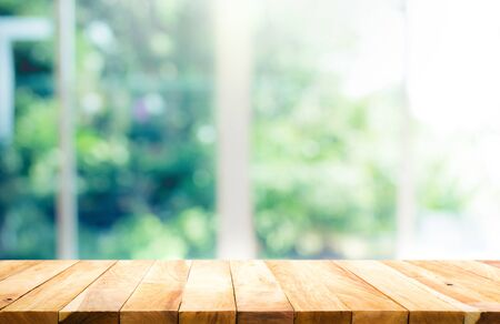 Wood table top on blur of window with garden flower background in morning.For montage product display or design key visual layout Stock fotó