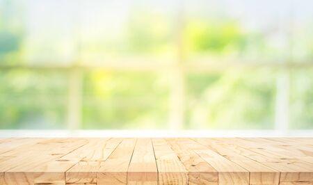 Leere Holztischplatte auf unscharfem abstrakten grünen Garten aus der Fensteransicht am Morgen. Für Montage-Produktdisplays oder Design-Key-Visual-Layouts