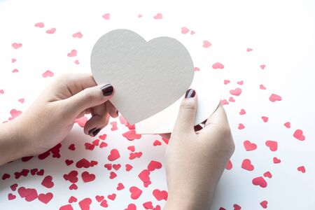 Female with white paper heart shape on small red hearts background.love,valentine,wedding concepts ideas