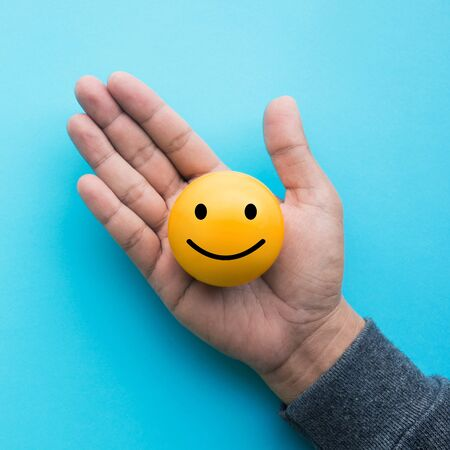 Male hand holding yellow  emoticon ball on blue color background