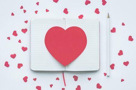 Red heart shape on white notepad background.love,valentine,wedding concepts ideas