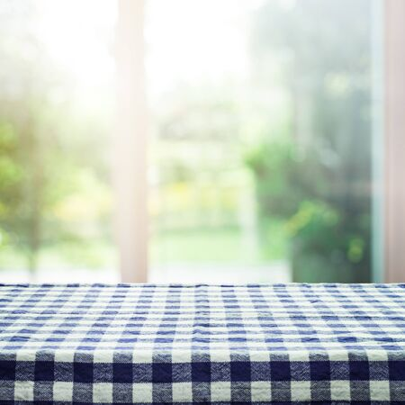 Checkered tablecloth texture top on blur of window and garden background in morning,homey style.For montage product display or design key visual layout