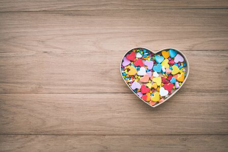 Colorful heart shape in box on wood table background.love, valentine,wedding concepts ideas