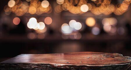 Blat z fakturą drewna (licznik) z rozmyciem jasnego złota bokeh w kawiarni, restauracji w tle. Do montażu wyświetlacza produktu lub projektowania kluczowego układu wizualnego