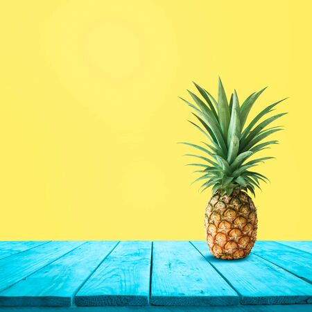 Pineapple on blue wood on yellow background.For montage product display or design keyvisual layout Zdjęcie Seryjne - 131789232