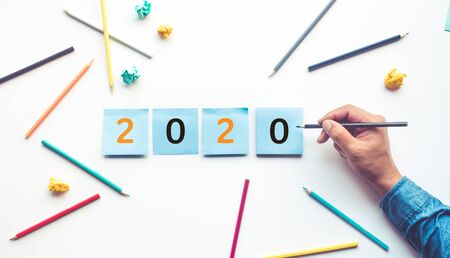 Business ideas 2020 with male hand writing text number on notepaper.New year new start concepts
