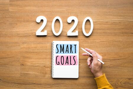2020, smart goal concepts with notepad and male hand on wood background.Business challenge.Inspiration ideas.Human performance