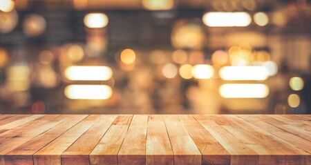Wood texture table top (counter bar) with blur light gold bokeh in cafe,restaurant background.For montage product display or design key visual layout