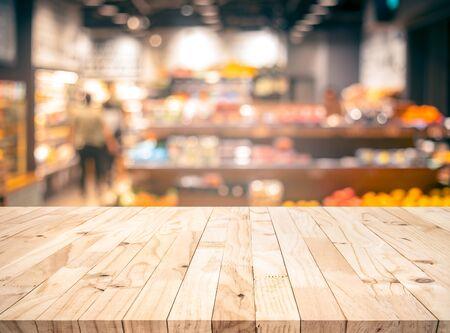 Blat z fakturą drewna (bar kontuarowy) z rozmyciem sklep spożywczy, tło sklepu na rynku. Do montażu produktu lub zaprojektowania kluczowego układu wizualnego
