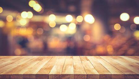Piano del tavolo con struttura in legno (bancone) con sfocatura bokeh oro chiaro nella caffetteria, sfondo del ristorante. Per la visualizzazione del prodotto di montaggio o il layout visivo chiave di progettazione