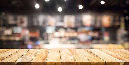 Piano del tavolo con struttura in legno (bancone) con sfocatura caffè, sfondo del ristorante. Per la visualizzazione del prodotto di montaggio o il layout visivo chiave di progettazione Archivio Fotografico
