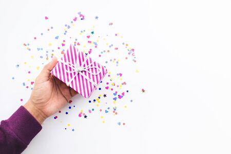 Celebration party and anniversary concepts ideas with young person hand giving gift box decoration with colorful confetti,paper art on white color background.copy space