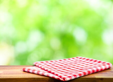 Red checked tablecloth on wood with blur green bokeh of tree background.Summer and picnic concepts.Design for key visual food and drink products.no people Imagens