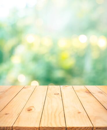 Real wood table top texture on blur leaf tree garden background.For create product display or design key visual layout