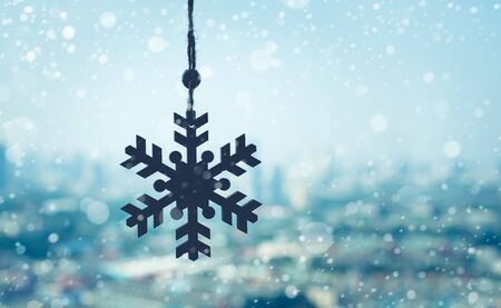 christmas ornament ( Snowflake ) hanging mobile with snowfall on blur outdoor landscape background.season and holiday concepts
