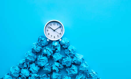 Timing and thinking idea with paper crumpled ball and white clock. business performance