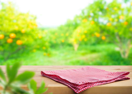 Red checked cloth on wood table top with blur of orange garden farm background.For montage product display or design key visual layout