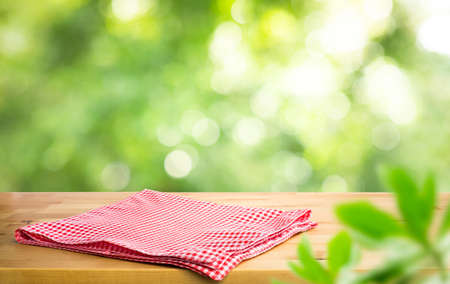Red checked tablecloth on wood with blur green bokeh of tree background.Summer and picnic concepts.Design for key visual food and drink products.