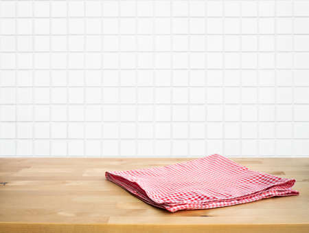 Red fabric,cloth on wood table top on blur white brick wall background of kitchen.For montage product display or design key visual layout.