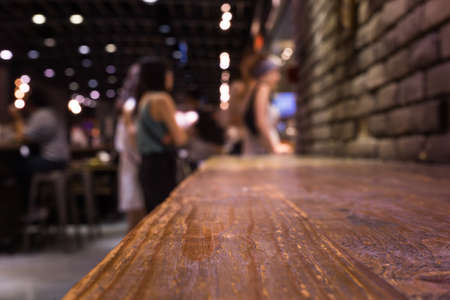Wood bar (table) on cafe in dark night with people and light background/selective focus.For montage product display