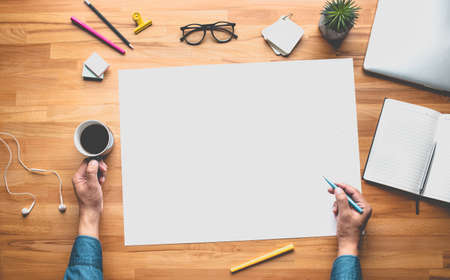 Top view of young person working on table with white space background.Business plan or creativity concepts Archivio Fotografico
