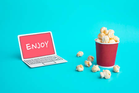 Enjoy with vdo entertainment or movie concepts with text on paper art laptop and pop corn on color background