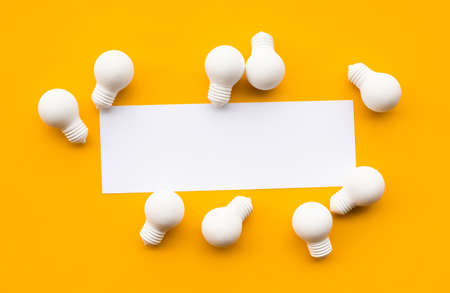 Business creativity and inspiration concepts with lightbulb and blank white paper on yellow background. motivation for success.think big ideas Stock Photo