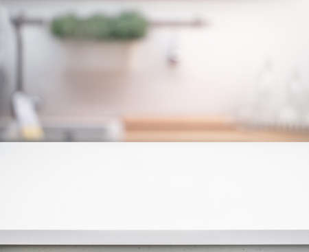 Selective focus/White table top on blur kitchen counter (room)background.For montage product display or design key visual layout. Archivio Fotografico