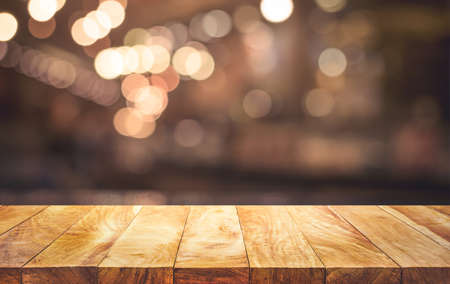 Wood table top (Bar) with blur light bokeh in dark night cafe,restaurant background.no people Archivio Fotografico