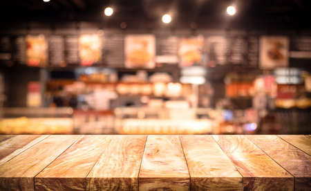 Wood table top (Bar) with blur light bokeh in dark night cafe,restaurant background.Lifestyle and celebration concepts ideas Archivio Fotografico