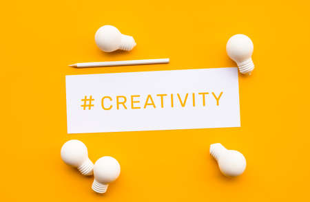 Business creativity concepts with text on notepaper and lightbulb on yellow background.motivation for success. Archivio Fotografico