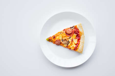 Top view a piece of pizza on white dish.Simple food and eating concepts