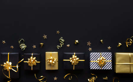 Merry christmas,xmas and new year celebration concepts with gift box and ornament in golden color on dark background.winter season and anniversary day Archivio Fotografico