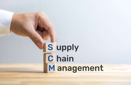 SCM text on wood box with male hand.business and  industry management.key to success Archivio Fotografico