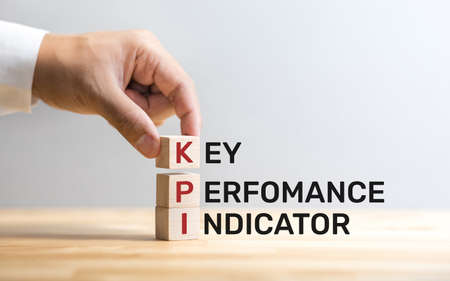 KPI text on wood box with male hand.business analysis.performance of strategy Archivio Fotografico