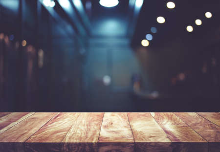 Wood table top on blurred of counter cafe shop with light bulb background. for montage product display or design key visual layout. Archivio Fotografico