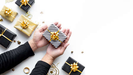 Merry christmas and new year celebration concepts with person hand holding gift box and ornament in golden color on white background.winter season and anniversary day