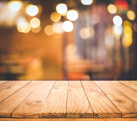Wood table top (Bar) with blur light bokeh in dark night cafe,restaurant background.copy space