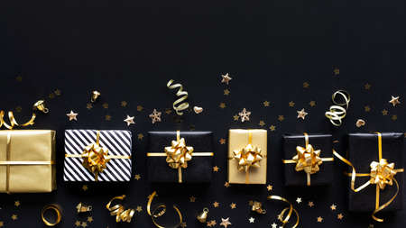 Merry christmas,xmas and new year celebration concepts with gift box and ornament in golden color on dark background.winter season and anniversary day 免版税图像