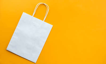 Shopping concepts with white bag paper on on yellow background.copy space