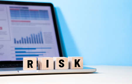Risk and  business management concepts with text on wood box on laptop.copy space