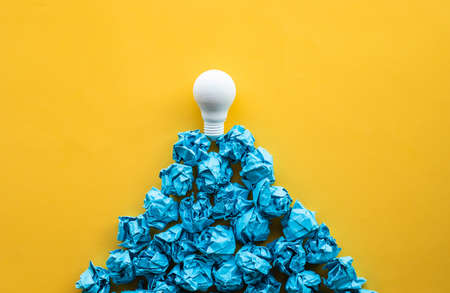 Idea and creativity concepts with lightbulb on top of paper crumpled ball in mountain shape.Think out of box.Business solution.