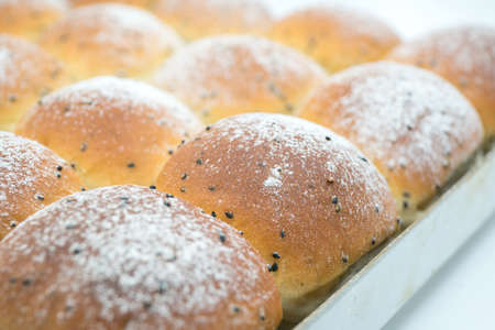 delicious breads with sesame seeds on the baking pan