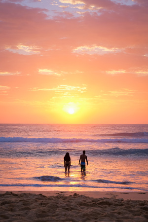 Couple in the water at the beach at sunrise