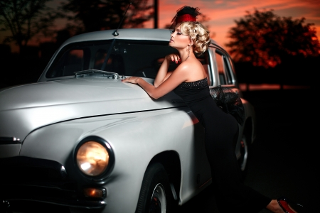 High fashion look glamor closeup portrait of beautiful sexy stylish blond  girl model with bright makeup in retro style posing near car behind sunset photo