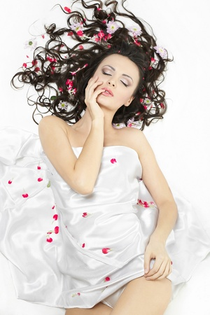 happy beautiful young brunette girl covered with bed sheet in bright flowers isolated on white photo