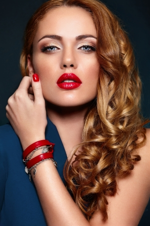 High fashion look glamor closeup portrait of beautiful sexy stylish blond Caucasian young woman model with bright makeup, with red lips,  with perfect clean skin with colorful accessories Stock Photo