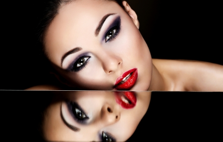 High fashion look glamour fashion portrait of beautiful sexy brunette girl female model with bright makeup and red lips and her reflection in mirror table on dark with perfect skin photo